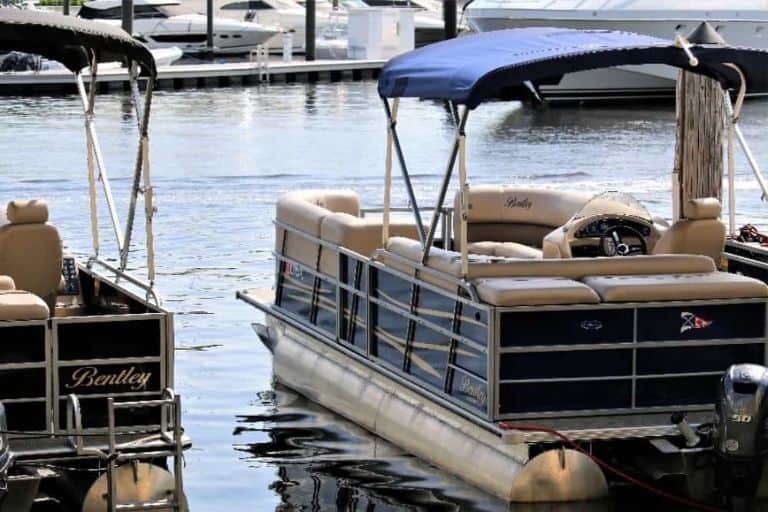 Image of blue and black Bentley pontoon boats side by side at the dock