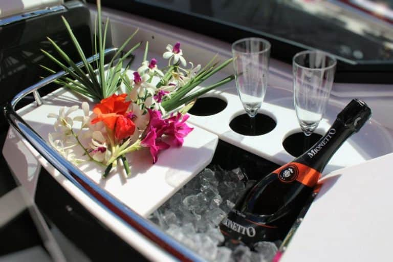 Close up image of rental boat wet bar with Champagne bottle, glasses and bouquet of flowers