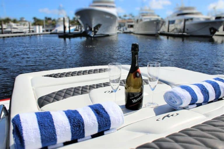 Image of champagne bottle with glasses and rolled towels on aft sunpad with superyachts in the background